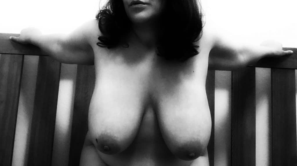 Topless tit pic: Kneeling in front of the headboard, arms stretched backwards to hold on to it
