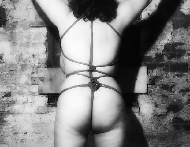 B&W nude from behind: rope harness and side-boob in front of old cellar coal hole.